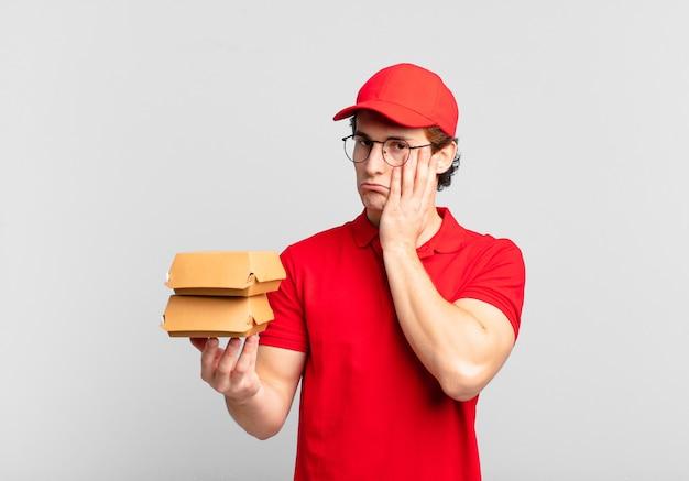 Hambúrgueres entregam o menino sentindo-se entediado, frustrado e com sono depois de uma tarefa cansativa, enfadonha e tediosa, segurando o rosto com a mão