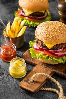 Hambúrgueres frescos de alto ângulo com batatas fritas e molhos