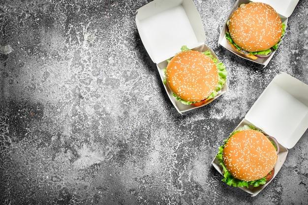 Hambúrgueres frescos em caixas de papel. sobre uma mesa rústica.