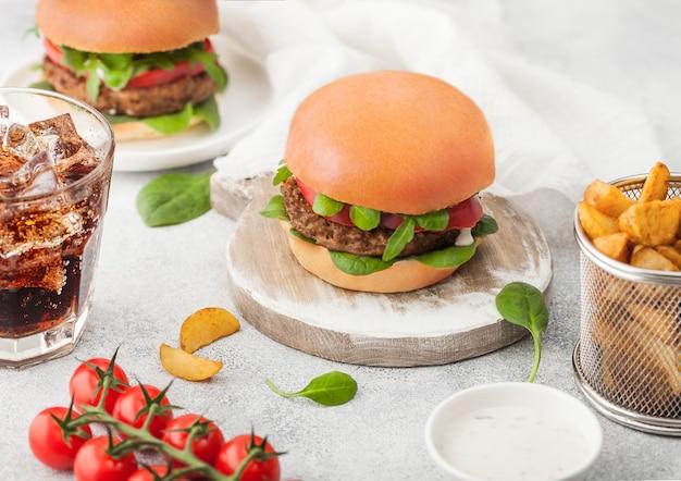 Hambúrgueres grátis de carne vegetariana saudável na tábua redonda com legumes sobre fundo claro com fatias de batata e copo de coca-cola e tomate cereja.