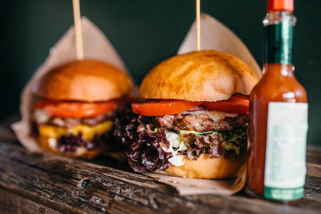 Hambúrgueres grelhados frescos e ketchup na mesa, closeup.