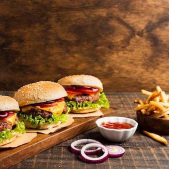 Hambúrgueres na bandeja de madeira com batatas fritas