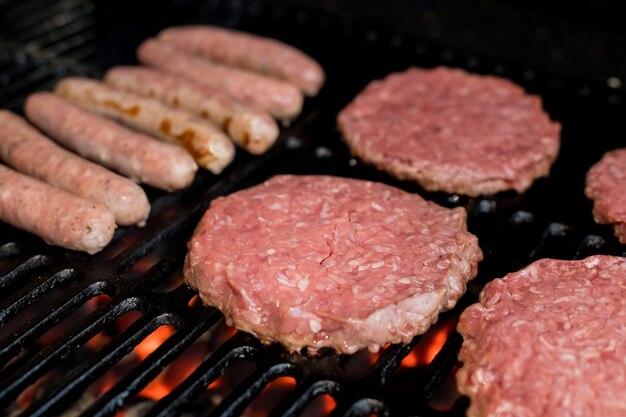 Hambúrgueres na grelha. alguns hambúrgueres frescos e suculentos cozinhando na grelha. hambúrgueres de carne sendo cozidos