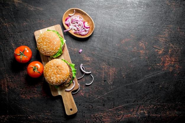 Hambúrgueres na tábua e fatias de cebola na tigela. em fundo rústico