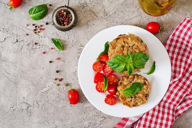 Hambúrgueres picantes vegan com arroz, grão de bico e ervas. tomate e manjericão da salada. comida vegetariana.
