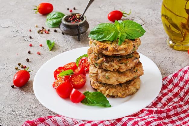 Hambúrgueres picantes vegan com arroz, grão de bico e ervas. tomate e manjericão da salada.