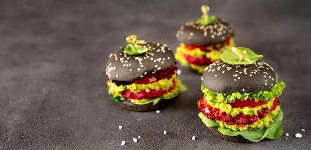 Hambúrgueres pretos veganos com rissóis de beterraba na superfície escura