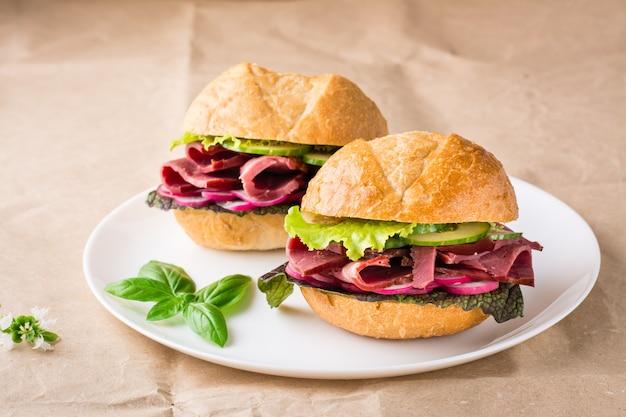 Hambúrgueres prontos para comer com pastrami, vegetais e manjericão em um prato de papel artesanal. fast food americano.
