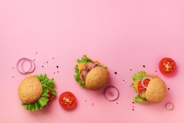 Hambúrgueres saborosos com carne, tomate, queijo, cebola, pepino e alface no fundo rosa.
