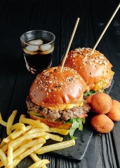 Hambúrgueres suculentos caseiros na placa de madeira