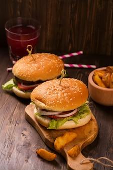 Hambúrgueres suculentos e perfumados com batatas fritas na mesa rústica de madeira