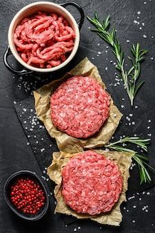 Hambúrgueres triturados crus do bife da carne handmade. fazenda de carne orgânica. fundo preto. vista do topo
