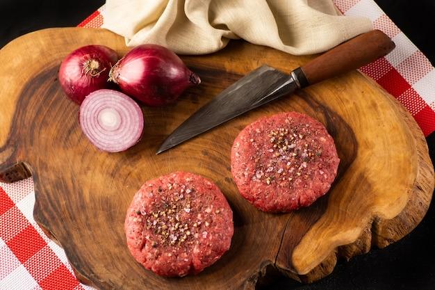 Hambúrgueres triturados crus feitos à mão do bife. fazenda de carne orgânica. fundo de madeira vista do topo