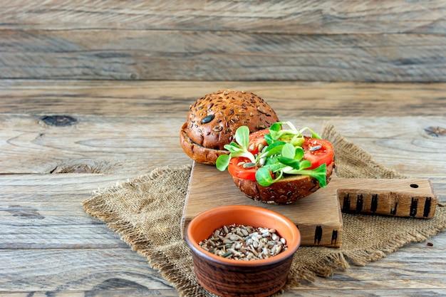 Hambúrgueres veganos com salada de milho e tomate em um fundo de madeira. conceito de alimentos com base em plantas.