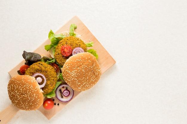 Hambúrgueres veganos na placa de madeira com espaço de cópia