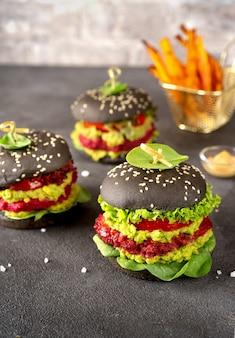Hambúrgueres veganos pretos com rissóis de beterraba e abacate na superfície escura