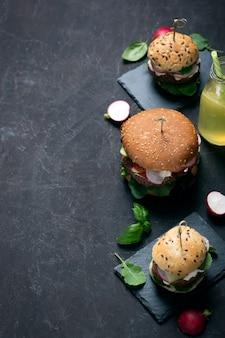 Hambúrgueres vegetarianos com legumes frescos e limonada caseira em cima da mesa