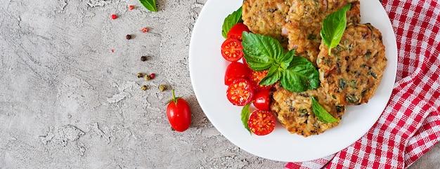 Hambúrgueres vegetarianos picantes com arroz, grão de bico e ervas. salada de tomate e manjericão. comida vegetariana. vista do topo. configuração plana