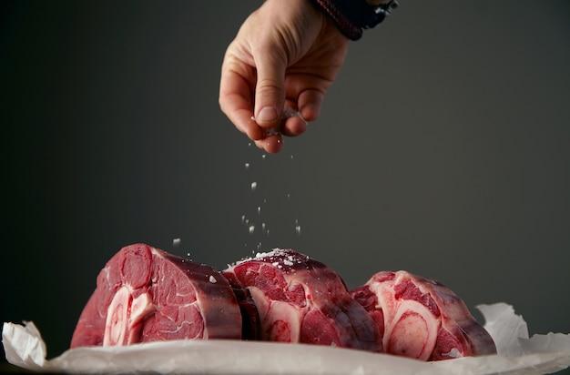 Hand está preparando três bifes de carne fresca com osso