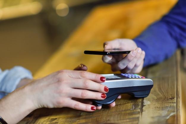 Hand holding smartphone pagando na máquina edc.