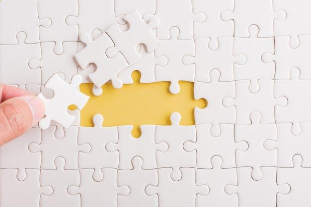 Hand-holding última peça livro branco quebra-cabeças últimas peças colocadas