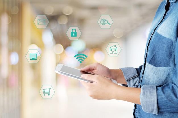 Hand using tablet with internet do ícone de coisas em fundo borrado, conceito de negócios e tecnologia