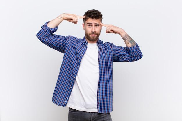 Handosme jovem homem com um olhar sério e concentrado, brainstorming e pensando em um problema desafiador contra a parede de cor lisa