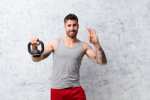 Handosme jovem homem contra a parede com um conceito de esporte haltere
