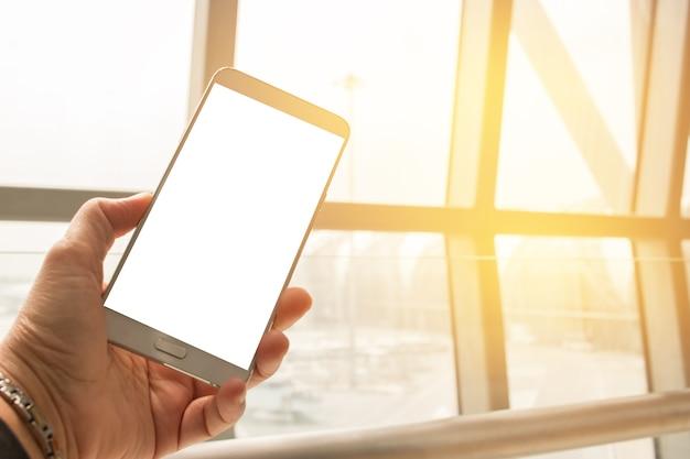 Hands holding usa o telefone inteligente no avião fundo borrado
