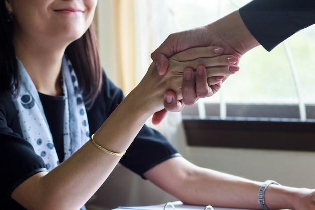 Handshake de negócios com mulheres de sorriso.