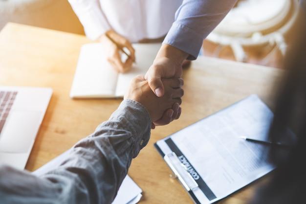 Handshaking de dois empresários em reunião após acordo de acordo final do projeto feito.