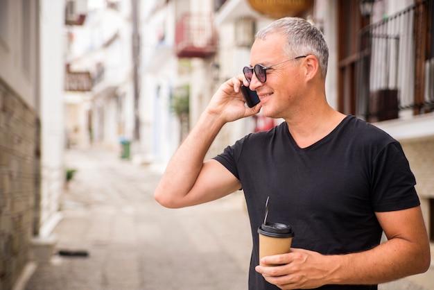 Handsome businessman falando no telefone e tomando café