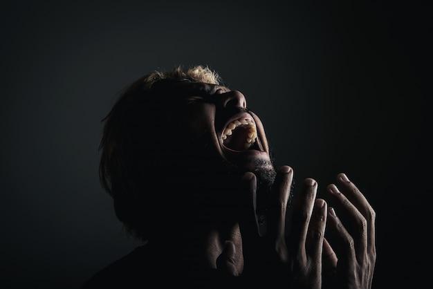 Handsome empresário gritando como um louco, stressed com o trabalho. retrato do estúdio de encontro ao fundo preto.