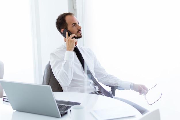 Handsome young man trabalhando com laptop e celular no escritório.