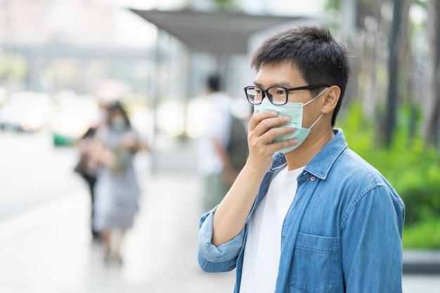 Handsomeman usando máscara facial protege o filtro contra a poluição do ar (pm2.5) ou usa a máscara n95. proteger