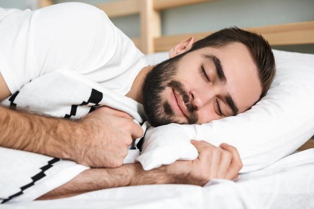 Handsonme sorrindo homem dormindo sobre um travesseiro na cama