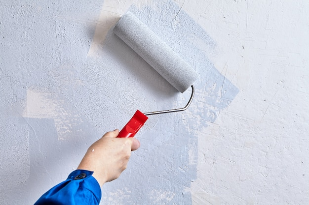 Handyman está pintando a parede com a ajuda de rolo de pintura e tintas durante a reforma