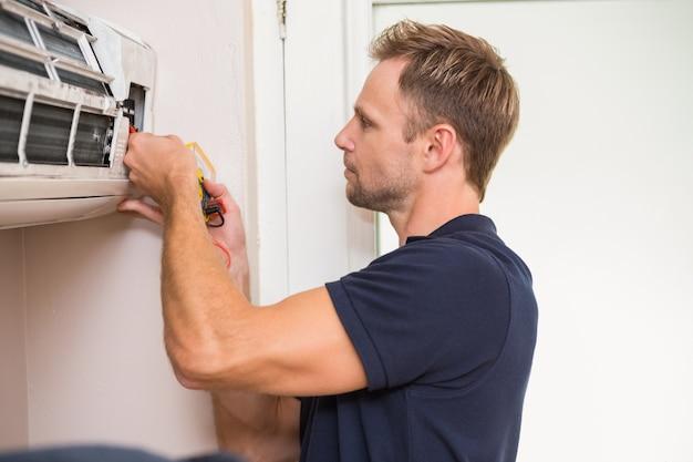 Handyman focado testando ar condicionado