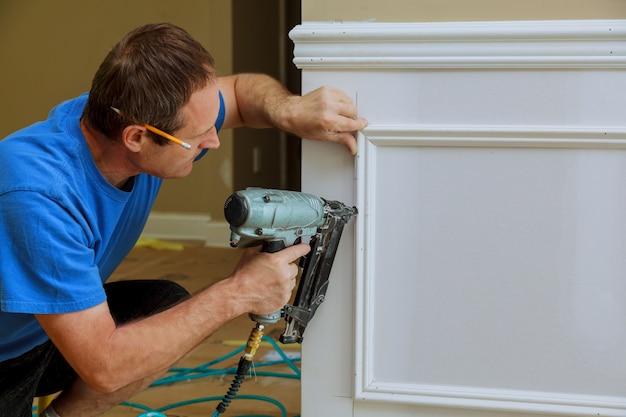 Handyman pregado na parede de moldagem na casa nova