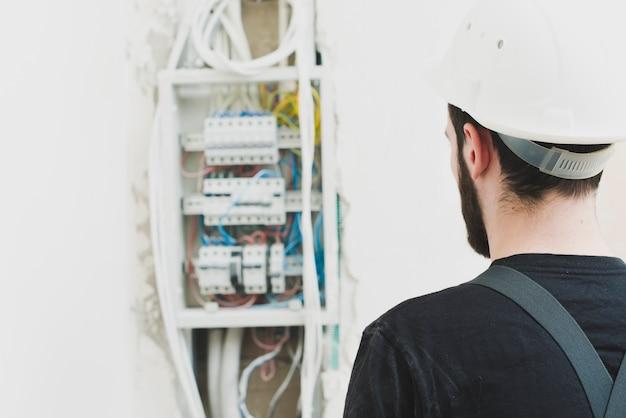 Handyman que olha o quadro de distribuição