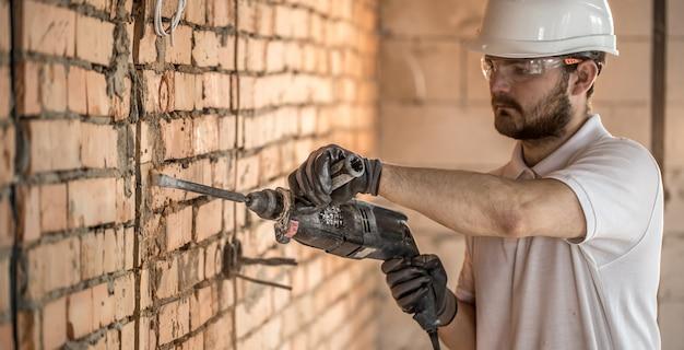 Handyman usa britadeira, para instalação, trabalhador profissional no canteiro de obras. o conceito de eletricista e faz-tudo.