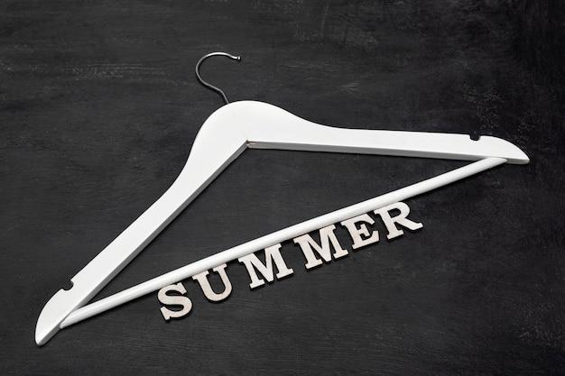Hanger de casaco de madeira branco e inscrição de verão em fundo preto. coleção de verão. venda de roupas de verão.