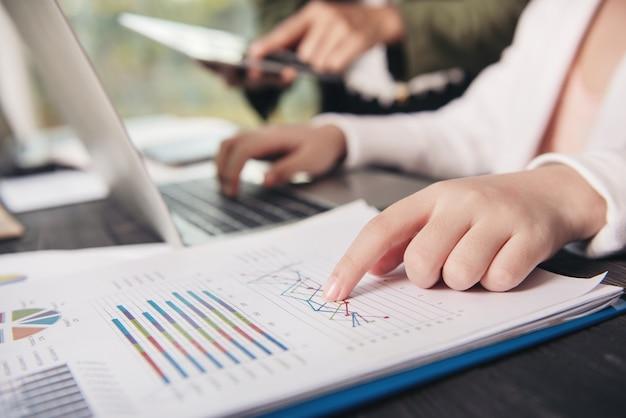 Hans de mulher de negócios sentado trabalhando, digitando teclado laptop. empresários reunidos no escritório escrevendo memorandos em notas autoadesivas.