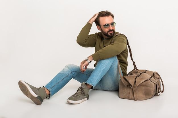 Hansome barbudo homem elegante sentado no chão isolado, vestido com moletom e bolsa de viagem, usando jeans e óculos escuros