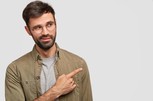 Hansome homem caucasiano com a barba por fazer olha curiosamente para o lado, indica com o dedo indicador no canto superior direito