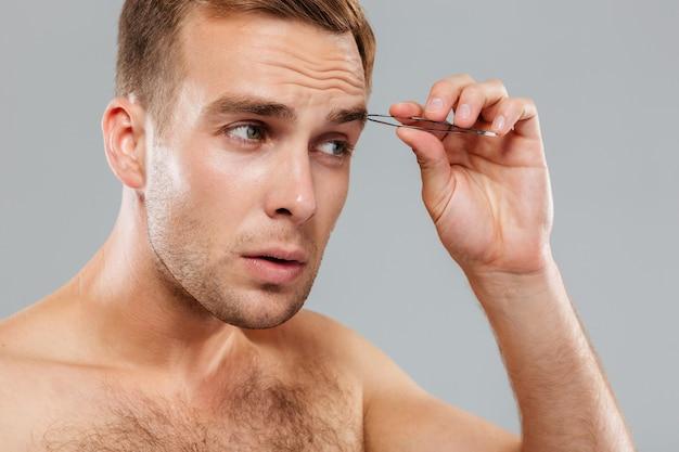 Hansome jovem sério removendo os pelos da sobrancelha com uma pinça