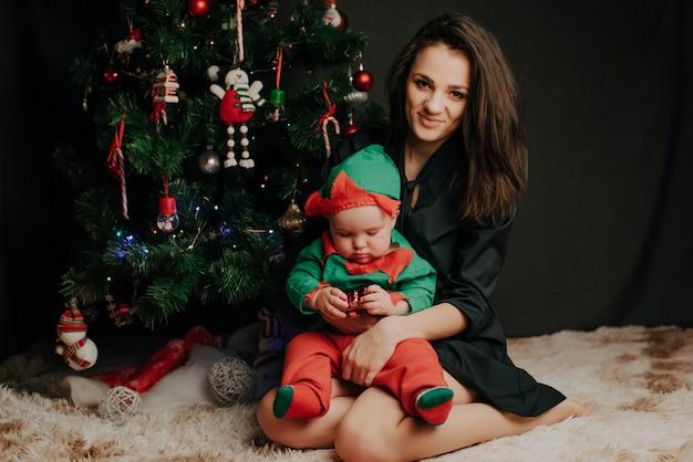 Happ mãe sentada com o bebê menino filho na árvore de natal