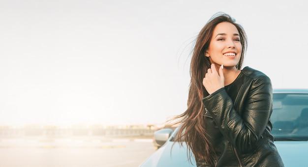 Happpy linda morena encantadora cabelos longos jovem mulher asiática na jaqueta de couro preta