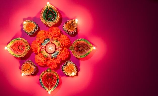 Happy diwali - lâmpada de óleo tradicional colorida diya em fundo rosa