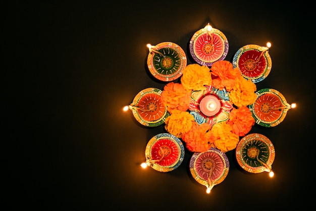 Happy diwali - lâmpadas de clay diya acesas durante dipavali, celebração do festival hindu